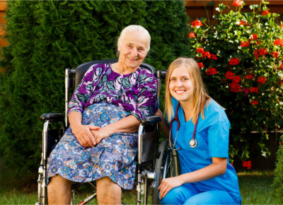Nurse and an elderly in wheelchair smiling