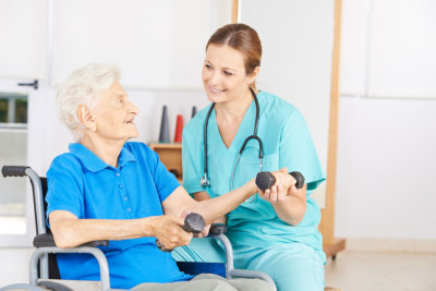 Caregiver is assisting the elder woman in her exercise