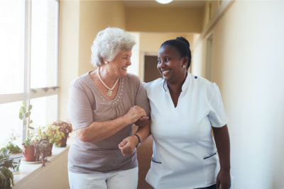 Caregiver assisting the elder in walking
